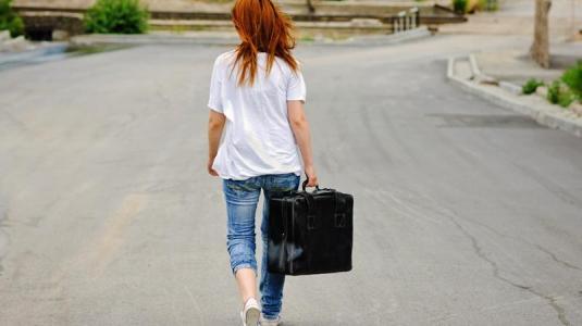 frau mit koffer im nirgendwo