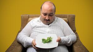 dicker Mann sieht traurig auf einen Teller Salat