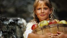 Mädchen mit Korb voller Äpfel