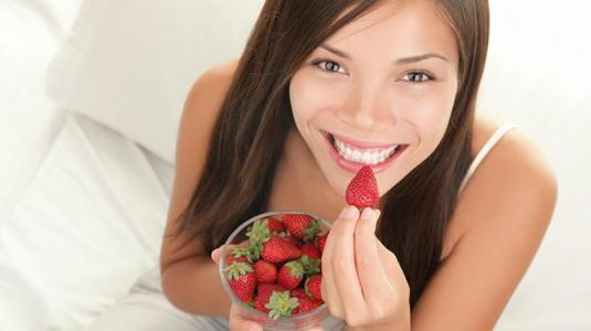frau isst erdbeeren
