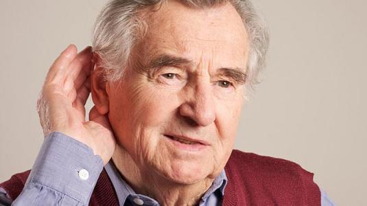 Alter Mann hält sich die Hand ans Ohr