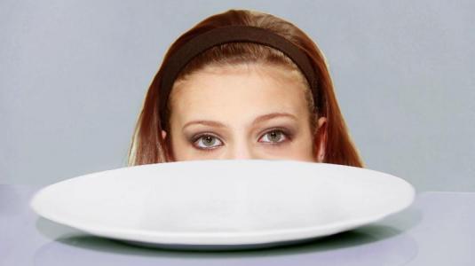 Frau vor leerem Teller