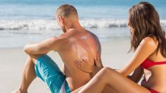 Frau cremt Mann mit Sonnencreme ein