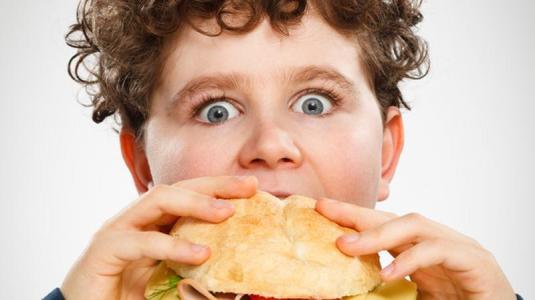 übergewichtiger junge isst hambuger